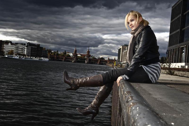 Mirjam Weichselbraun sitzt auf Kaimauer in Berlin.